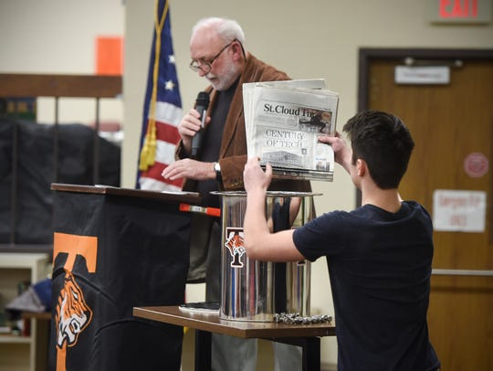 Copies of the St. Cloud Times are placed into a time