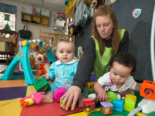 Emily Brink, an infant's teacher at KinderWorld, keeps a watchful eye on Laila Sjodin, left, and Myah Thurman, right, as the children play.