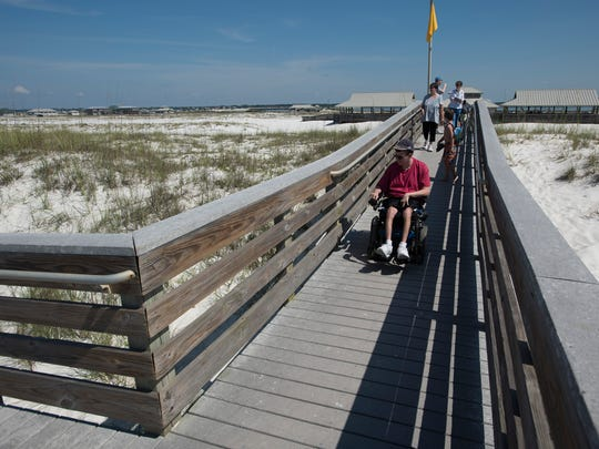Navarre resident Brad Alexander navigates the boardwalk ramp at Navarre Beach on Thursday, June 8, 2017.