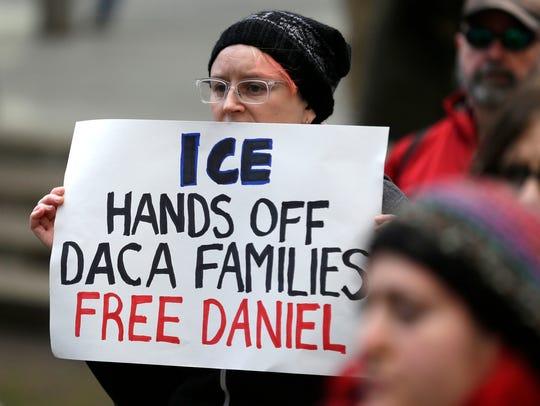 Una mujer sostiene una pancarta que dice 'ICE no te