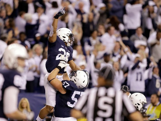 Penn State's Steven Gonzalez (57) lifts teammate Saquon Barkley after Barkley scored a touchdown. Gonzalez is one of four returning starters on the Nittany Lions' offensive line. AP FILE PHOTO