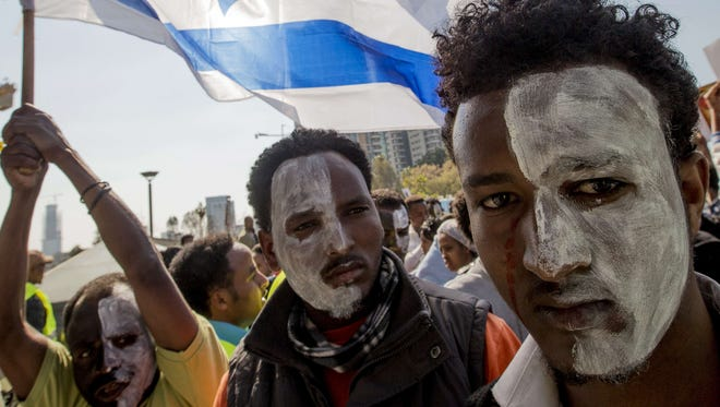 African asylum seekers, who entered Israel illegally via Egypt, wave an Israeli national flag as they take part in a protest in front of the Interior Ministry in the Mediterranean coastal city of Tel Aviv on Feb. 11, 2014, after several days of mass protests against Israel's immigration policies.