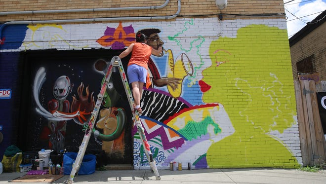 Lady Pink works on her mural on the side wall of Pancho Villa Deli and Mexican Restaurant in the City of Poughkeepsie. She was brought in to paint the mural as part of the second annual O+ Festival.