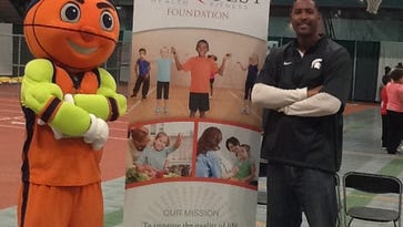 Andre Hutson poses next to a sign for his Conquest Health Fitness Foundation.