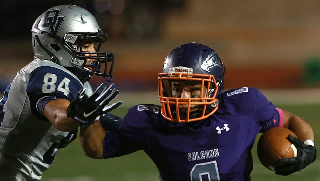 Eastlake running back Adrian Chavez, right, pushes away from Del Valle defender Angel Estrada after taking a lateral from a teammate on the way to a touchdown on a hook-and-ladder play near the end of the first half Thursday.