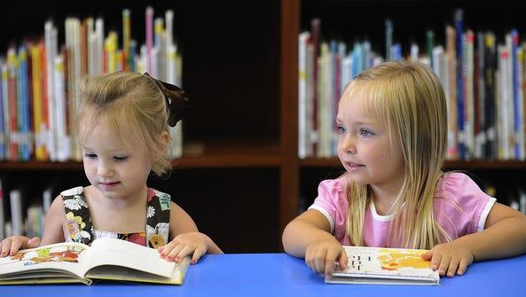 Julie Boshell, left, and Katelynn Brannon look at books