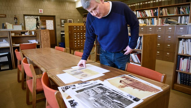 """Stearns History Museum head archivist Steve Penick looks over photographs Tuesday, April 25, that could be included in a history display during an """"open courthouse"""" event Friday at the Stearns County Courthouse in St. Cloud."""