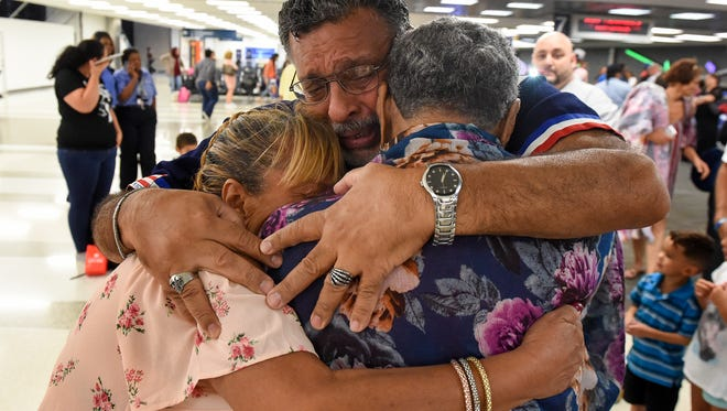 """""""Thank you, God. Thank you, God,"""" repeated a tearful Julio Sanchez Jr. of Palm Bay (center) as he and his sister, Iris Sanchez of Kissimmee (left), greet their mother, Amelia Sanchez of Vega Baja, Puerto Rico, Wednesday, Oct. 04, 2017, after her arrival to Florida via San Juan at the Fort Lauderdale-Hollywood International Airport."""
