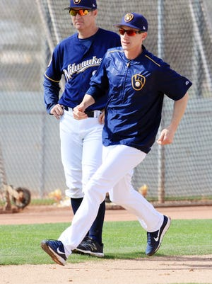 Brewers manager Craig Counsell fills in as a base runner, in front of instructor Charlie Greene, during spring training drills Wednesday.