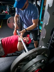 Trainer Victor Grant spots powerlifter Brandon Sanford as he bench presses at Victor's Gym in Pensacola on Thursday, May 24, 2018.  Sanford is preparing to compete in the national Special Olympics USA Games this summer in Seattle.