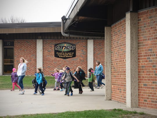 Students walk out the front school doors to board buses