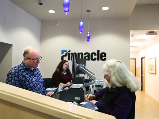 Pinnacle Financial Partners service specialist Johnny Thompson assists customer Gail Zacharias during a transaction in Germantown on Wednesday morning.