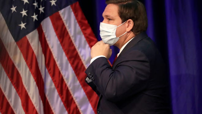 Florida Gov. Ron DeSantis puts on his mask to protect against the new coronavirus as he leaves a news conference on COVID-19, Friday, June 19, 2020, at Florida International University in Miami.