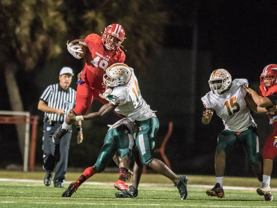 Dunbar 's Rocky Jacques-Louis tackles Abraham Alce