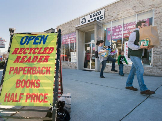 Shoppers leave Recycled Reader in York loaded with books during a going-out-of-business sale. Owners Irene and Phil Ritson are retiring and closing the shop after 25 years, the last 22 at a location on East Market Street.