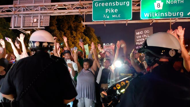 "Protesters chant ""Hands up! Don't shoot!"" at motorcycle officers near the head of a line of vehicles stuck on Interstate 376 in Pittsburgh on Thursday, June 21, 2018. The highway was shut down by the people protesting the East Pittsburgh police after the June 19 shooting death by police of Antwon Rose, a 17-year-old boy."