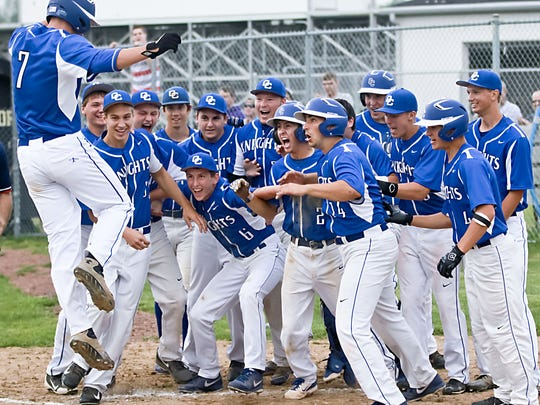 Members of the Oak Creek baseball team prepare to celebrate as Doran Turchin jumps onto home plate after hitting a grand slam during a game in 2014. Turchin was our only two-time All-Suburban Player of the Year for baseball.