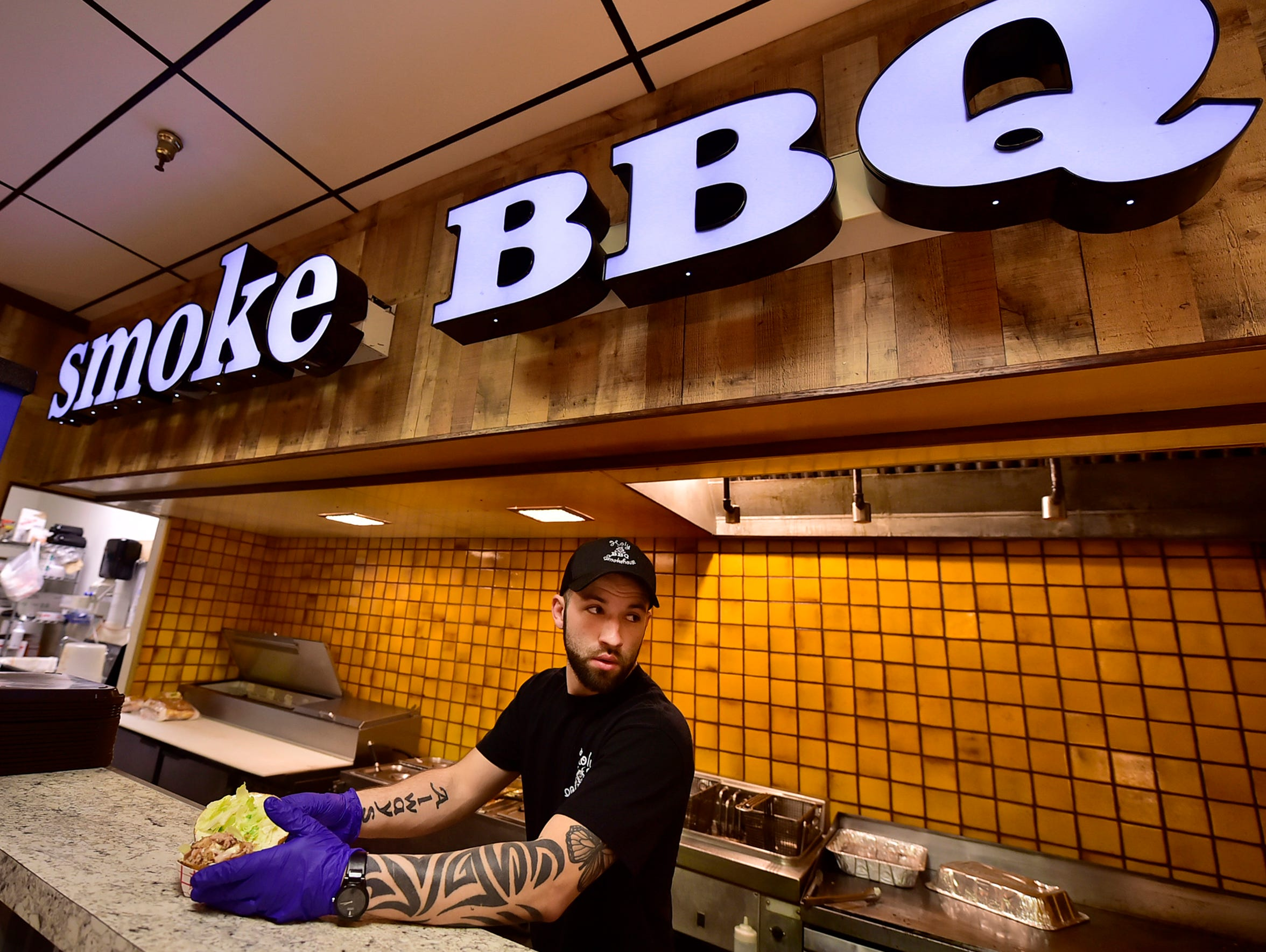 Austin Little prepares food at Holy Smokehouse BBQ on Wedensday, April 25, 2018. Bon-Ton is closing and many anchor stores have left Chambersburg Mall. The future of the mall, and other malls nationally, could be impacted by store closings.
