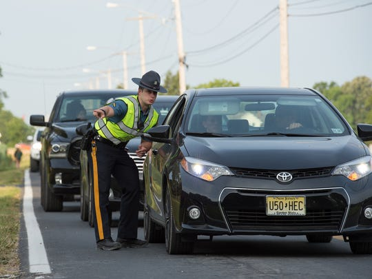 Delaware State Trooper, TFC. Benjamin Nefosky stops cars along Persimmon Tree Lane at the 2017 Firefly Music Festival in Dover.
