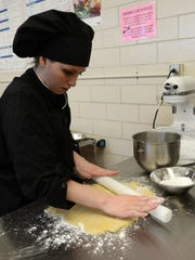 Bailee McCall rolls sugar cookie dough Thursday, March