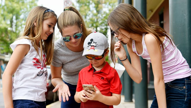 Sarah Mock of West Manchester Township, second from left, watches with her daughters Molly, 9, far left, and Emily 12, as son Harry, 6, manages to get into the Pokemon Go game on Sarah's smartphone during a widespread server outage Saturday, July 16, 2016, in York. Downtown Inc had planned a Downtown York Pokemon Lure Party, but the outage resulted in the event being moved to Saturday, July 23.