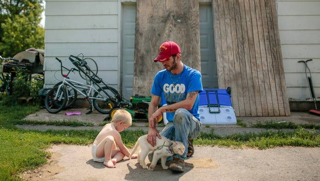 "Tom Chobanian, 29, sits with his cat and his 2-year-old son, Tommy, outside his home in Donken, Mich., on Aug. 20, 2017. The former lumber town is all but abandoned now. ""I love it. Oh, I love it. You don't even know ,"" he said. ""I love just the peace and quiet, just the wind blowing."""