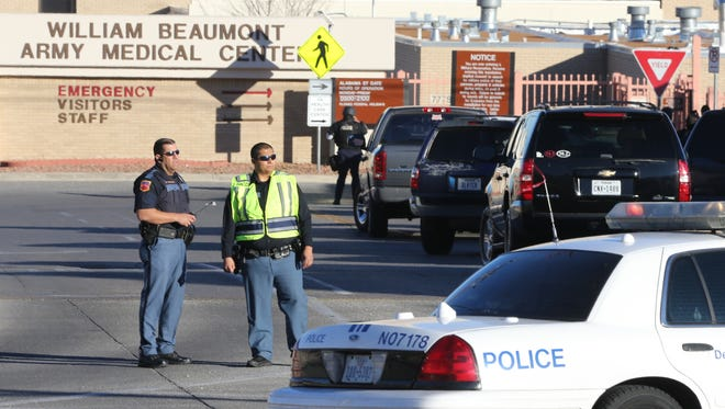Police officers guard an entrance to the Beaumont Army Medical Center/El Paso VA campus during the search for a gunman Tuesday, Jan. 6, 2014. (AP Photo/The El Paso Times, Victor Calzada) ORG XMIT: TXELP102