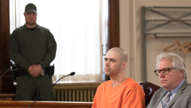 A Department of Rehabilitation and Correction SWAT officer closely stands watch as Casey Pigge, middle, and his lawyer Steven Larson, right, listen as Judge Randall Knece sentences Pigge to 25-years-to-life in prison after he pleaded guilty to killing David L Johnson on a prison bus earlier this year .