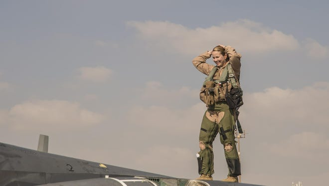 Maj. Jennifer, a 391st Expeditionary Fighter Squadron weapon systems officer, stands on top of an F-15E Strike Eagle following a combat sortie at an undisclosed location in Southwest Asia, Feb. 13. Jennifer surpassed the 1,000 combat-flight hour mark during the mission in support of Operation Inherent Resolve.