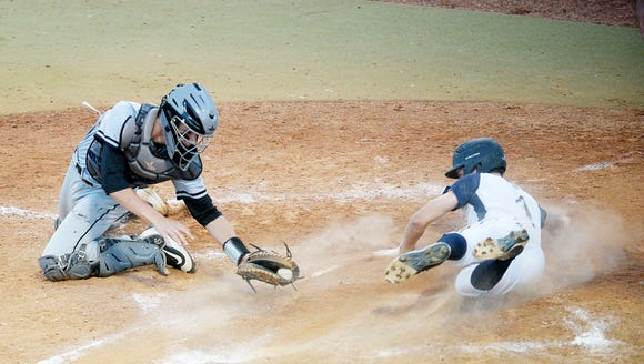 Roberson's Drew Elliot slides across home plate as