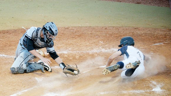 Roberson's Drew Elliot slides across home plate as Rockingham County's Austin Paynter attempts to tag him May 9, 2018.