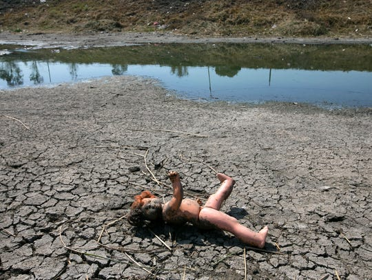 A doll lies in the mud along the banks of the Remedios