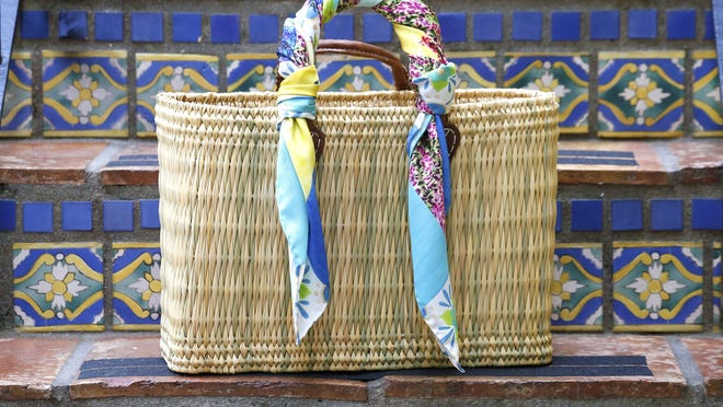 Banniere's silk scarves can be styled more than one way. Here, one is  wrapped around a bag's handle.