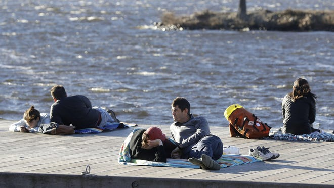 Phil Taneyhill, center right, and his wife Elisa, center left, both of Boston, sit on a dock in the Charles River Esplanade park, in Boston, Sunday, Jan. 12, 2020, while enjoying unseasonably warm weather. Temperatures climbed into the low 70s in many places in the state Sunday.