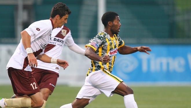 Rhino's Levi Houapeu (16) carries the ball away from Scaramento's Nemanja Vukovic (12).