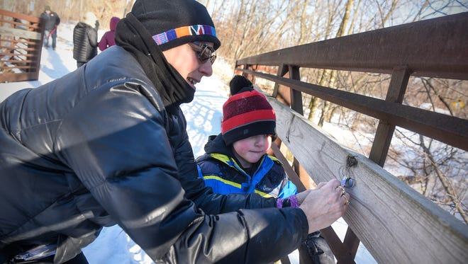 Aiden Bauer and Janell Bauer locate a Park Blast Scavenger Hunt ticket on foot bridge while hiking at Rockville County Park and Nature Preserve Friday, Feb. 9, in Rockville.