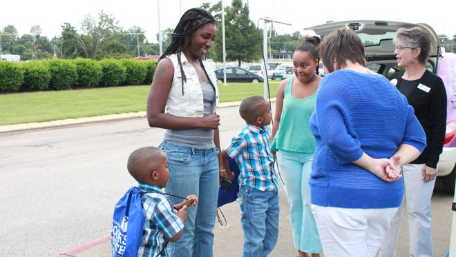 "Children receive backpacks Saturday at the Jackson Fairgrounds Park from the ""Books from Birth 10 th  Anniversary Tour."""