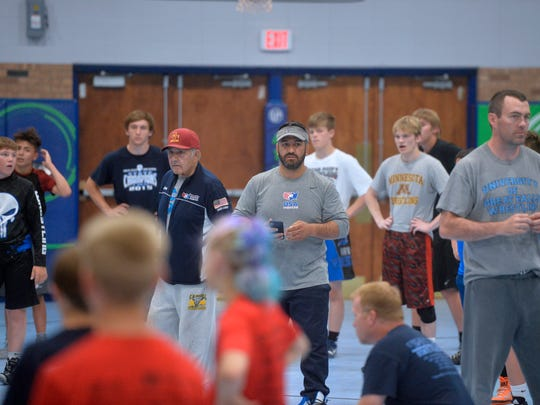 Bob Zadick, center-left, helps out his sons, Bill and Mike, with their camp, the Zadick Brothers' Wrestling Camp, at University of Providence on Tuesday.