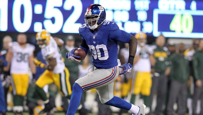 New York Giants defensive end Jason Pierre-Paul (90) runs back an interception against the Green Bay Packers for a touchdown during the fourth quarter of a 2013 game at MetLife Stadium.