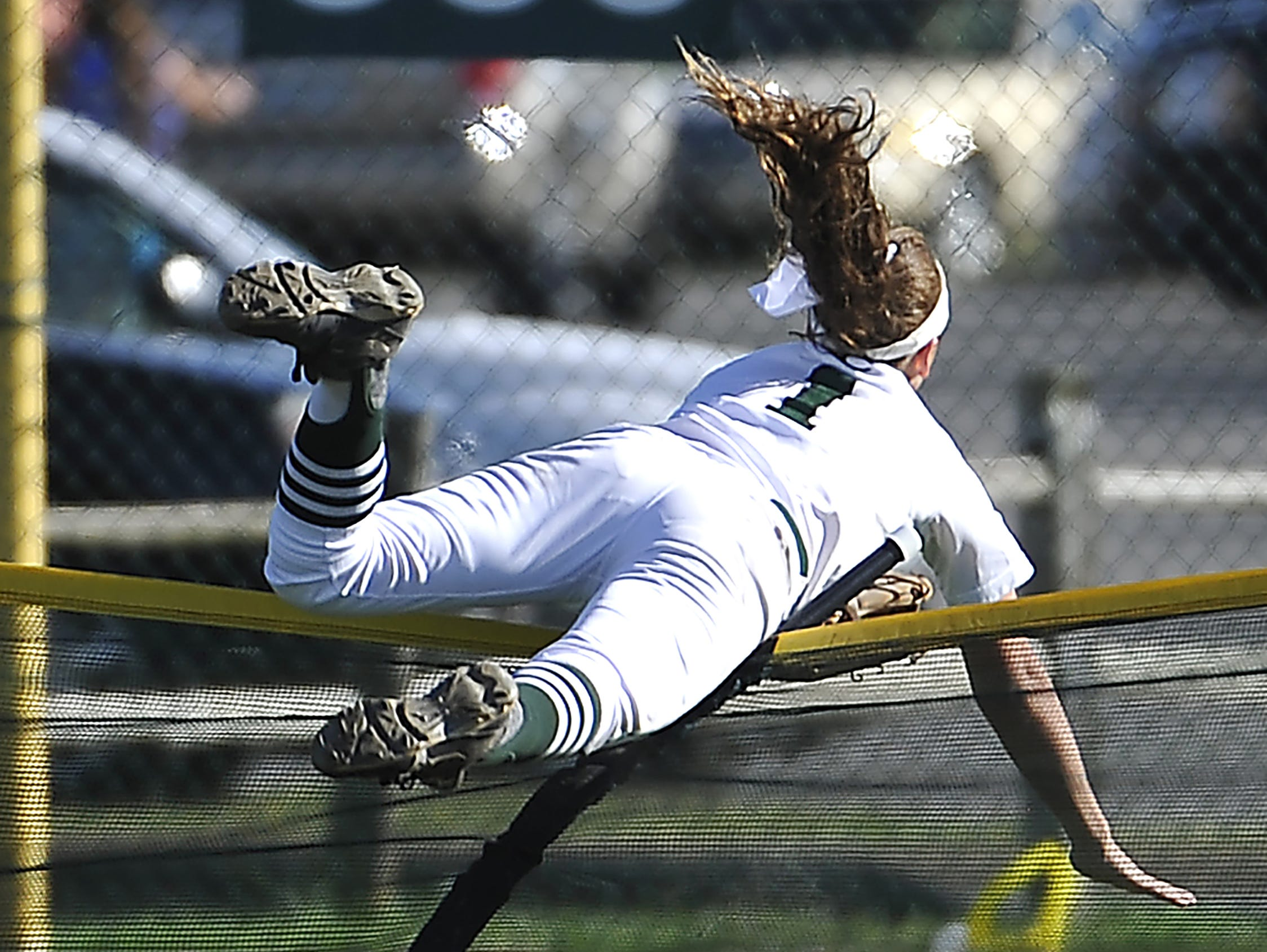 Outfielder Brooke Eakes goes over the fence after catching what would have been a home run as Friendship Christian plays Kings Academy in the A championship game Friday.