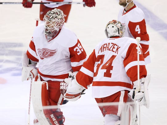 Red Wings goalie Petr Mrazek (34) is brought to the