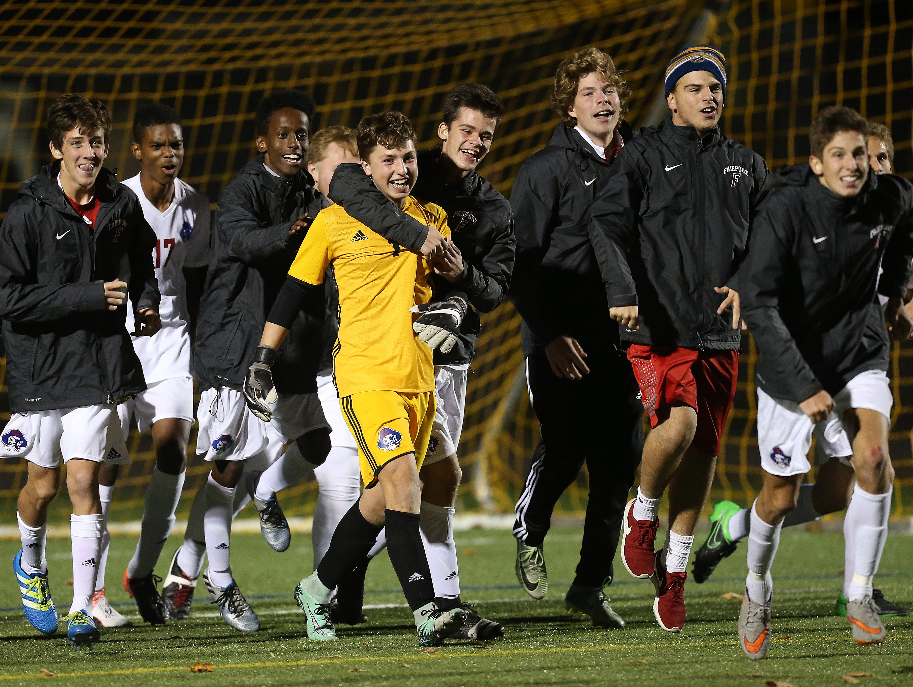 Fairport keeper Jake Horst is congratulated after the Red Raiders beat Webster Thomas 2-1 to win the Class AA title. Horst made a big save in the final seconds of the game to protect the lead.