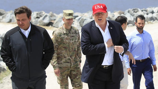 President Donald Trump walks with Florida Gov. Ron DeSantis (left) during a visit to Lake Okeechobee and Herbert Hoover Dike at Canal Point, on March 29, 2019. Sen. Marco Rubio (in back) talks with Donald Trump Jr.