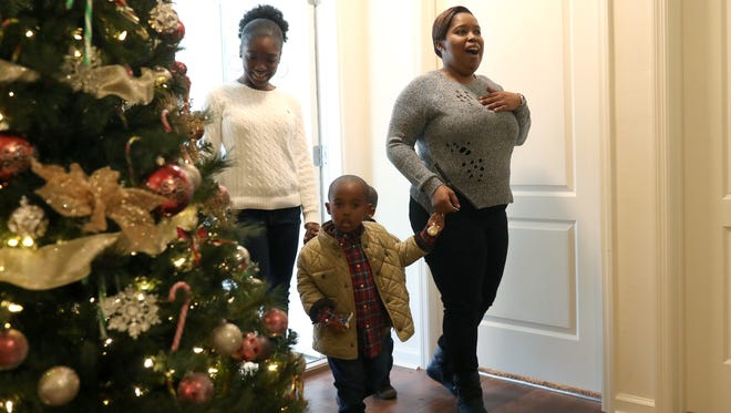 India Williams is surprised with a fully furnished home for her and her 3 children, twin 3-year-old boys Jeremiah and Joshua and 13-year-old daughter Asia on Wednesday. Williams was given the keys to her new home, which was built by Habitat for Humanity, along with the furnishings from Warrick Dunn Charity.