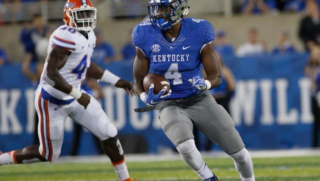 Sep 19, 2015; Lexington, KY, USA; Kentucky Wildcats running back Mikel Horton (4) runs the ball against the Florida Gators in the first quarter at Commonwealth Stadium. Mandatory Credit: Mark Zerof-USA TODAY Sports
