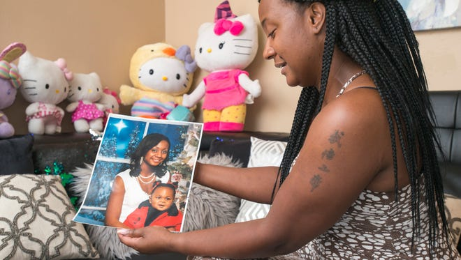 Shantara Hurry, the mother of Naomi Jones, shows photos of her daughter June 7 as she prepares for Naomi Jones Day. The 12-year-old girl was kidnapped and killed last year.