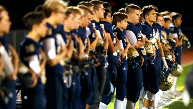 The Queen Creek Benjamin Franklin football team stands for the National Anthem before a high school football game against Florence Oct. 20, 2017.