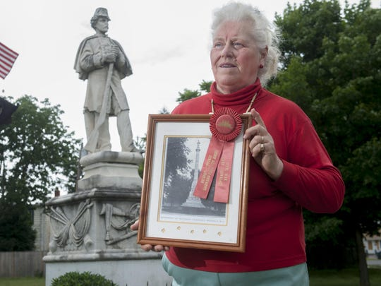 Beverly resident Carole Moore stands by the Civil War statue that is currently outside of the American Legion Post in Beverly. It once stood in the Beverly National Cemetery and guarded its Civil War dead but was removed. Moore is holding a photograph of the statue that was shot as the statue stood at the cemetery. 06.04.15