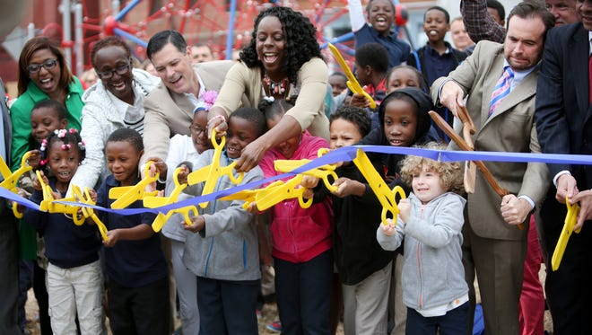 Students from Rothenberg Preparatory Academy help with a ribbon cutting during the grand reopening ceremony of the newly renovated Grant Park, in Over-the-Rhine on Thursday afternoon.
