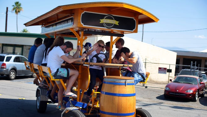 Laura Rovick, the owner of Social Cycle, leads a group from Los Angeles to tour Palm Springs on her human pedal powered vehicle on Wednesday.